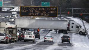 A truck blocks all east-bound lanes of Interstate 285 in suburban Atlanta on Jan. 29, 2014. Image: AP